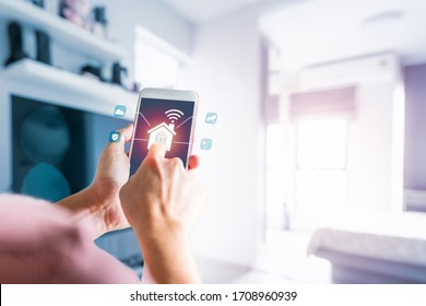 Man's finger touch the icon on smartphone screen, electronics devices connecting with wireless. Smart home control and Automation system technology of things