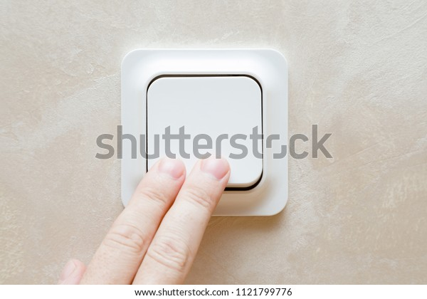 Man's fingers pressing light switch at the wall. Save energy at home.