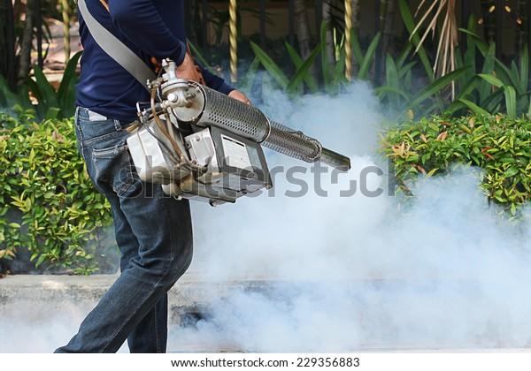 Man's fogging to eliminate mosquito for preventing spread dengue in village.