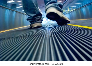 Man's foot walking in airport escalator perspective view (ground level)
