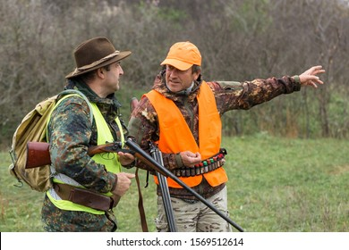 A mans with a gun in his hands and an orange vest on a pheasant hunt in a wooded area in cloudy weather. Hunters with dogs in search of game.