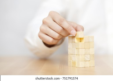 Man's hand adding the last missing wooden block into place. Business success concept.