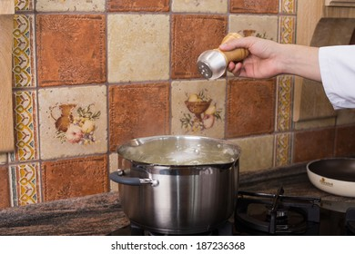 Man's hand adding salt into the hot water in the kitchen