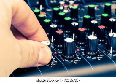 man's hand adjusting mixing console knobs close-up view