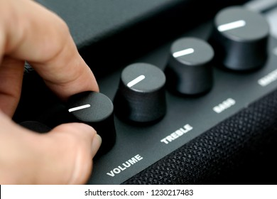 man's hand is adjusting the music volume from the amplifier.