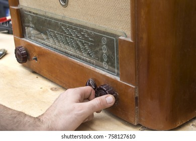 The man's hand adjusts the potentiometer scale in the old vintage radio tube.