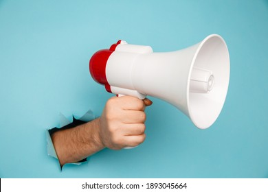 Man's hand arm hold megaphone isolated through torn blue background
