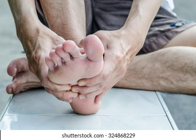 Man's hand being massaged a foot