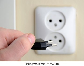 Man's hand with black electrical plug