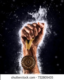 Man's hand in a blue fire is holding up gold medal on a dark background. Winner in a competition.