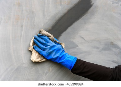 Man's hand in blue glove wipes a metal surface a rag. A trace from a rag on a surface.