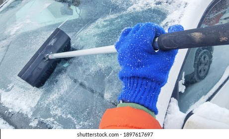 A man's hand in a blue knitted woolen glove and an orange jacket cleans the windshield of a car from snow.