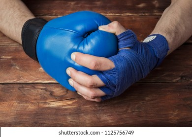 man's hand in boxing bandages holds a hand in a boxing glove on a wooden background. Ready gesture. The concept of training for boxing training or fighting. Flat lay, top view.