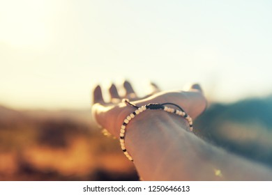 man's hand with bracelet stretches forward in the sun in anticipation of summer