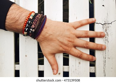 Man's hand with a lot of bracelets on white wooden table. Fashion accessories on the men's hand. Wooden bracelets, bracelets with beads and braided bracelet on men's hand. Men's fashion