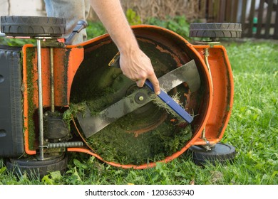 Man's hand with brush cleaning lawn mower
