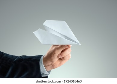 A man's hand in a business suit holds a paper airplane. Startup concept, light business, getting started. Copy space