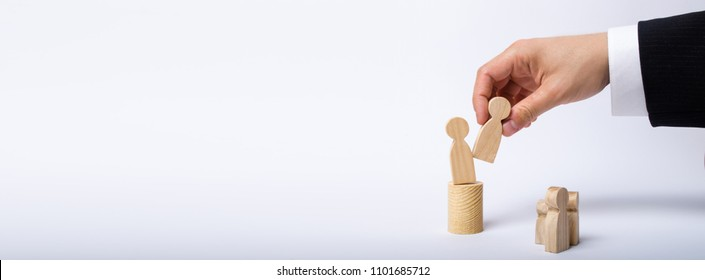 The man's hand of a businessman in a business suit holds a wooden figure of a man in his hand and moves another figure from his post. The concept of firing an employee, the replacement of staff Banner