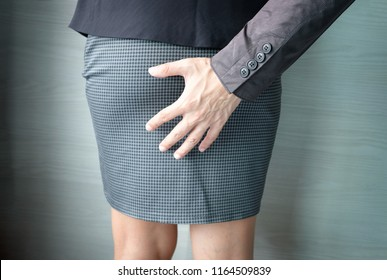 A man's hand catches a woman's an ass and leg of office girl. He is sexually abusing. Woman office wear short skirt be assaulted sexually. Mental Health and Sexual Abuse Concept.