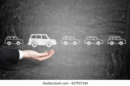Man's hand choosing white car sketch over row of black cars on chalkboard background. Concept of choice