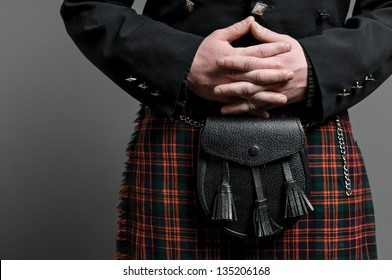 A man's hand clasped over a Scottish kilt and purse.