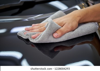 Man's hand cleaning car and drying vehicle with microfiber cloth. Hand wipe down paint surface of shiny black sedan after polishing and ceramic coating. Car detailing  and car wash concept.