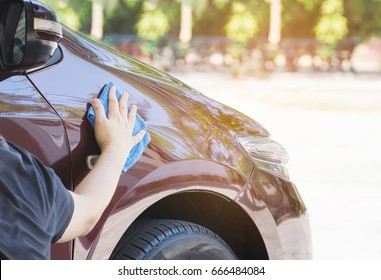 Man's hand is cleaning and waxing the car