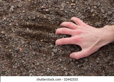 Man's hand clinging to a stony ground