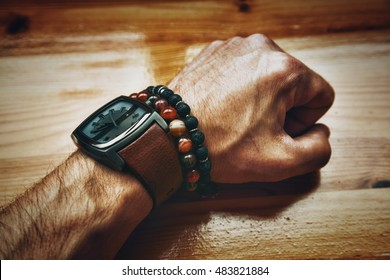 man's hand with clock closeup. compressed brutal male fist. Bracelets - jewelry agate stone and lava stone on the hand. Fashionable men's accessories and jewelry