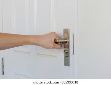 man's hand close the white door