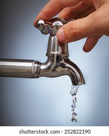 man's hand closes the leakage of water from the faucet Metal