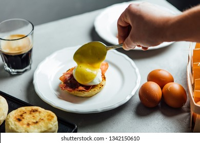 Man's hand coating surface of poached egg with hollandaise sauce