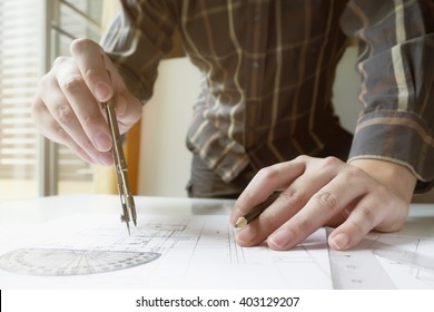 Man's hand with a compass. Mechanical engineer at work. Technical drawings. Pencil, compass, calculator and hand man. Paper with technical drawings and diagrams. User sunlight vintage retro filter