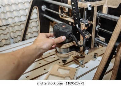 Man's hand at the computer numerical control machine for wooden tools. CNC equipment for maintenance control and details.