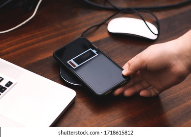 The man's hand connects the charger to his smartphone, with an office desk in the background。Wireless charging concept