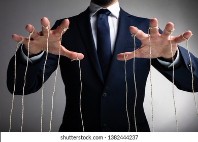 Man's Hand Controls The Puppet With The Fingers Attached To Threads Against Gray Background