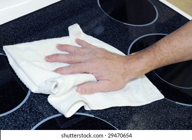 Man's hand with cotton terry towel cleaning ceramic cooktop