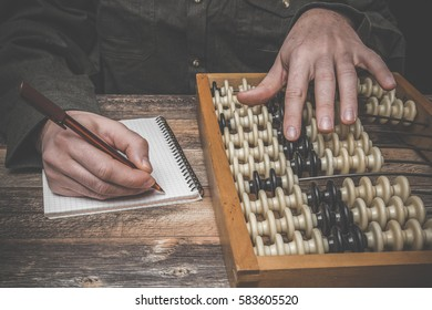 Man's hand counting with old abacus on the wooden table. Retro things.