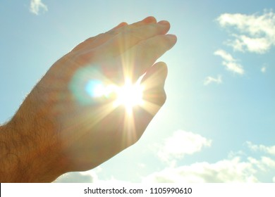 A man's hand covers a bright scorching sun. The sun shines through and dazzles through the hand. Close-up. Background.
