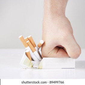 Man's hand crushing cigarettes