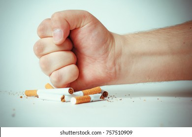 Man's hand crushing cigarettes. quit Smoking.
