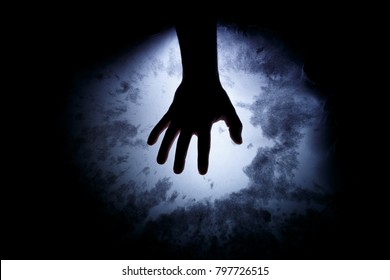 A man's hand in the dark. Supernatural situation. Abstract background for horror with magic.