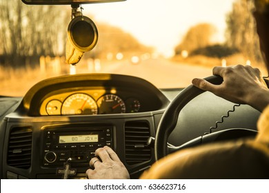 Man's hand driving a car at sunset evening sky light Autumn Road between trees forest Male sit inside control volume audio system Finger lie on wheel Empty copy space for inscription