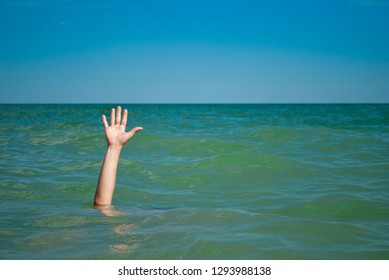 A man's hand drowns in water calling for help, against the background of the sea and sky clouds summer, sun, weekend, can not swim, rescue, vacation wave foam