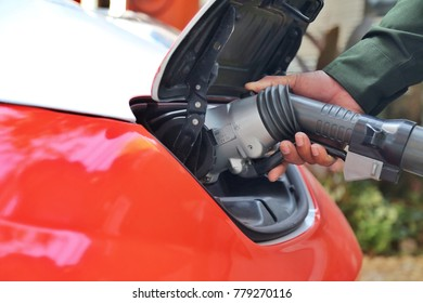 Man's hand with Electric car is charging at the charging station and it is the future of the Automobile.
