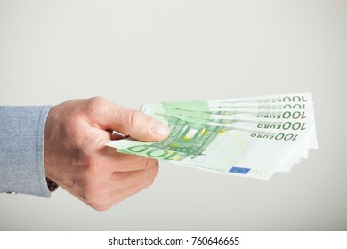 Man's hand extending euro banknotes - closeup shot on grey background