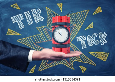 Man's hand facing up holding dynamite bundle with time bomb on blackboard background with chalk words 'tick tock'. Time is ticking away. Business waits for no man. Business is at risk.