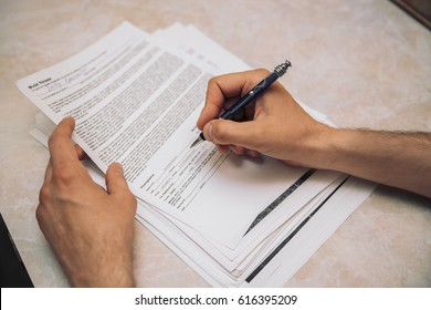 Man's hand is filling in document