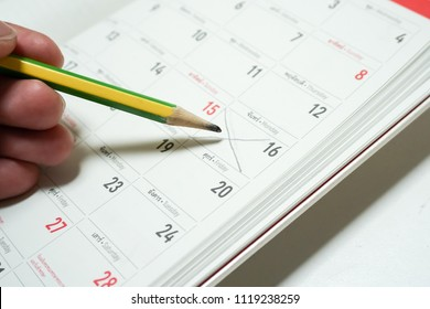 Man's hand fills date table writing with pencil on paper calenda
