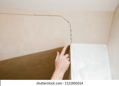 Man's hand finger pointing to the cracked wall in a house. Building problems and solutions concept.